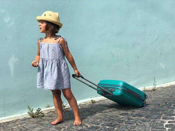 bambina che trascina valigia