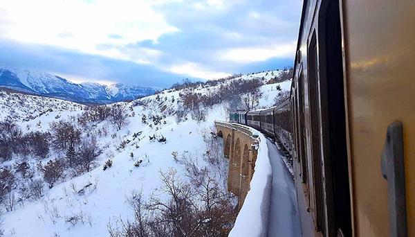 treno storico su ponte nella neve transiberiana