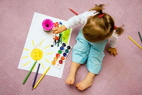 bambina disegna sole seduta per terra