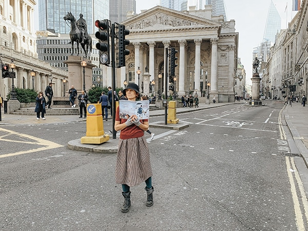 Donna per le strade di Londra con il libro di mary Poppins