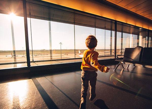 bambino di spalle mentre corre terminal aeroporto