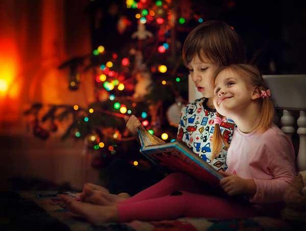 bambini leggono libro sotto albero di Natale