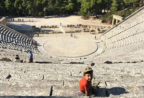bambino seduto con cappellino siullo sfondo teatro greco antico