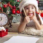 bambina scrive lettera a babbo natale, con cappello di natale