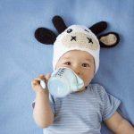 bambino con capppello a mucca beve latte