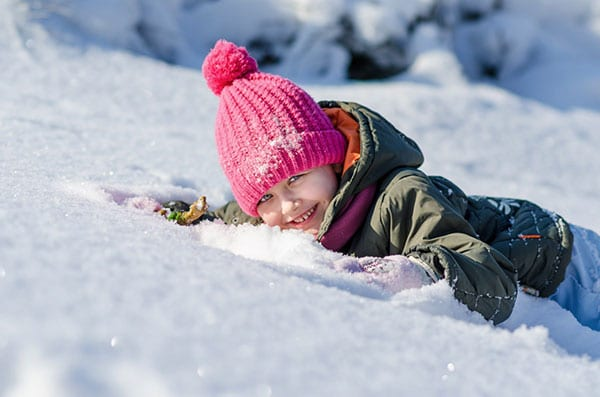 bambino ride con la faccia sulla neve