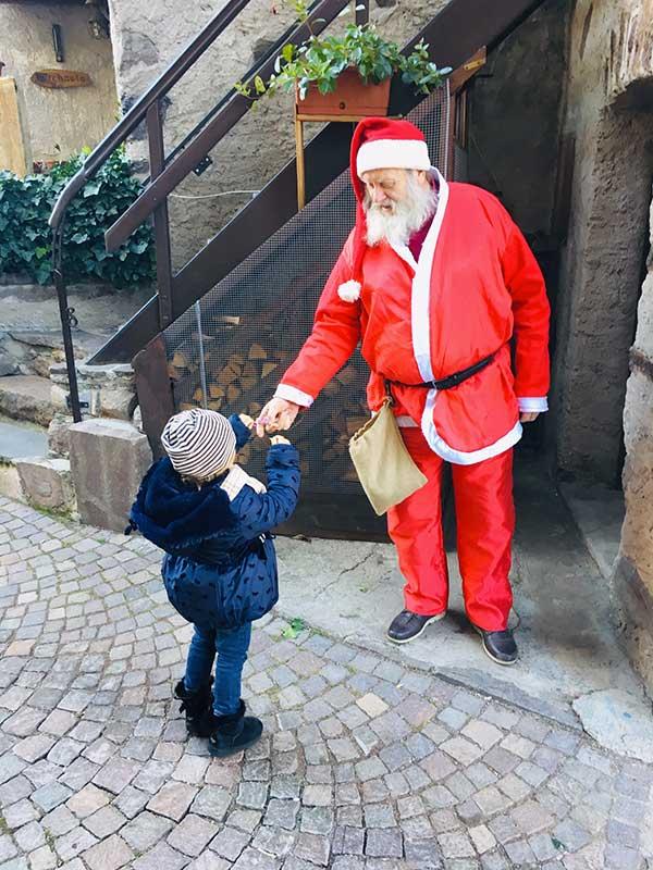 babbo natale dà una caramella a un bambino