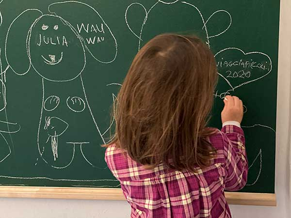 bambina scrive alla lavagna