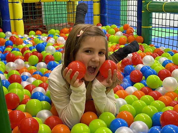 bambina tra le palline colorate