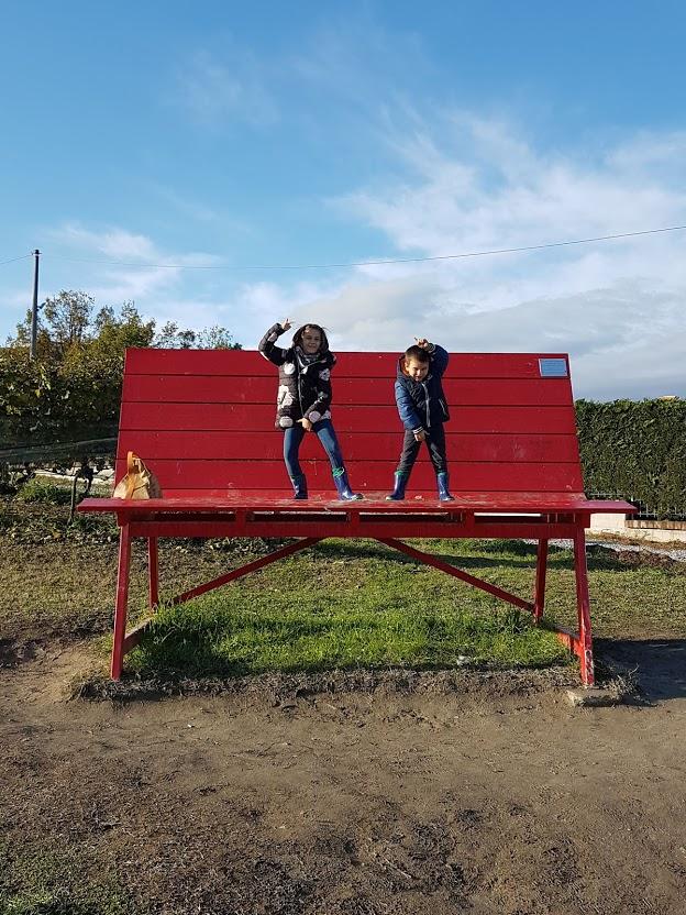 bambini su panchina gigante rossa
