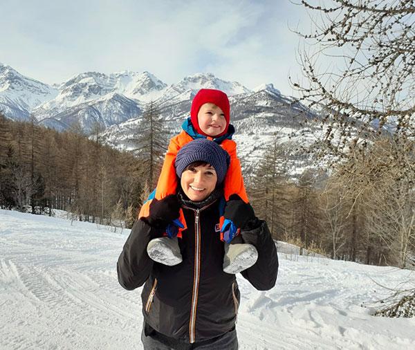 mamma con bambino sulle spalle nella neve