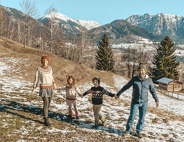 famiglia in primo piano sull osofndo le Dolomiti in inverno