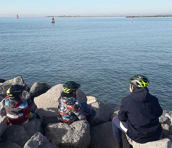 bambini di spalle co ncasco bici guardano il mare