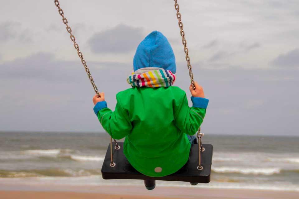 bambino sull'altalena in riva al mare d'inverno