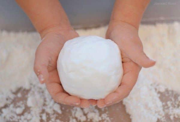 palla di neve finta e mani di bimbo