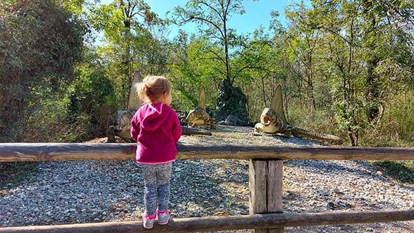 bambina che guarda ricostruzione di animali presitorici in un parco
