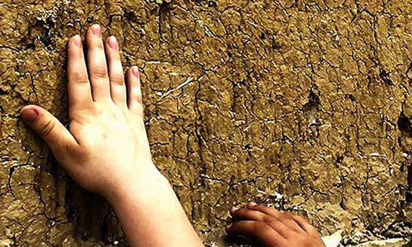mano di bimbo su parete di terra