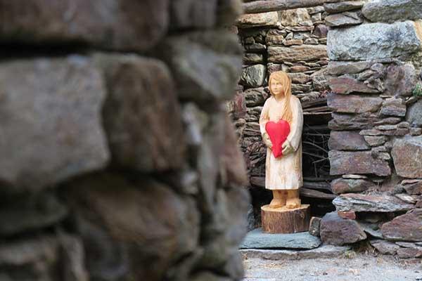 statua legno bambina con cuore a Chemp