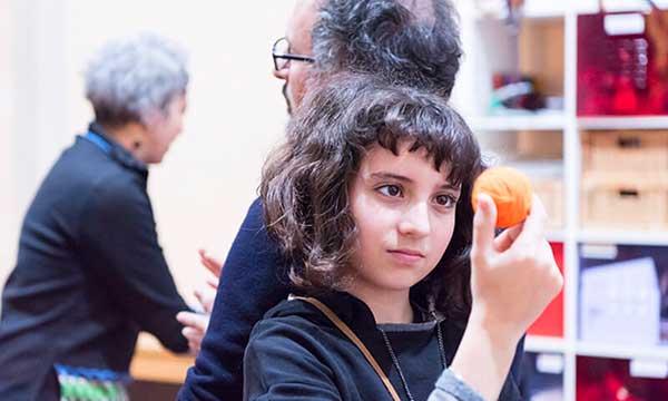 bambina al museo guarda una palla arancione