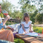 mamma e bambini in Toscana, mamma beve calice di vino e i bimbi disegnano