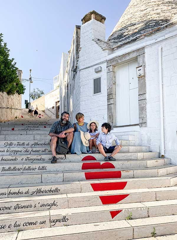 famiglia seduta su scale dove è dipinto un cuore