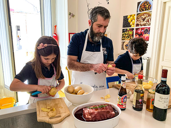 famiglia in cucina papà e bambini cucinano arista maiale
