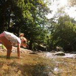 Bimba con i piedi nel fiume nel Parco fluviale del Vergari