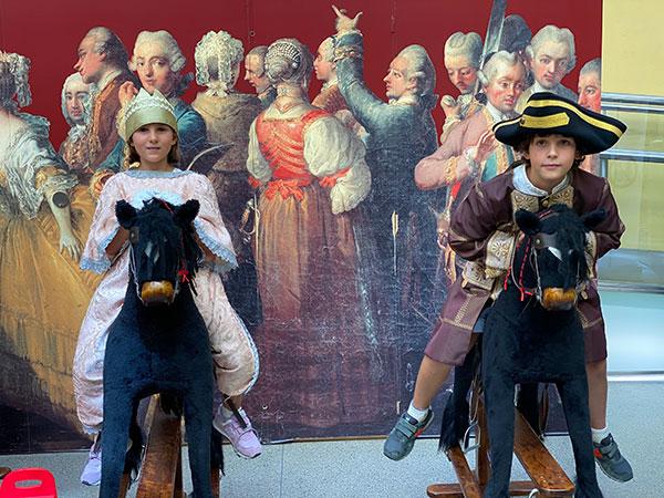 Musei per bambini a vienna-cover-viaggiapiccoli bambini vestiti in costume su cavalli a dondolo