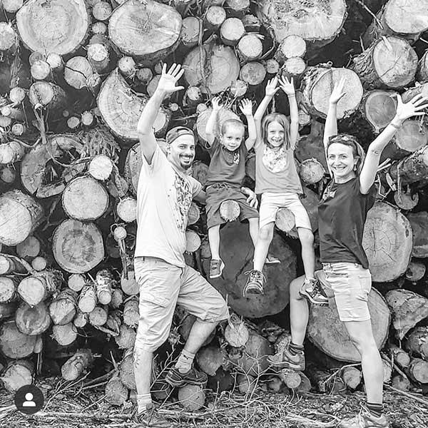 famiglia mamma papà e due bambini davanti a una catasta di legna