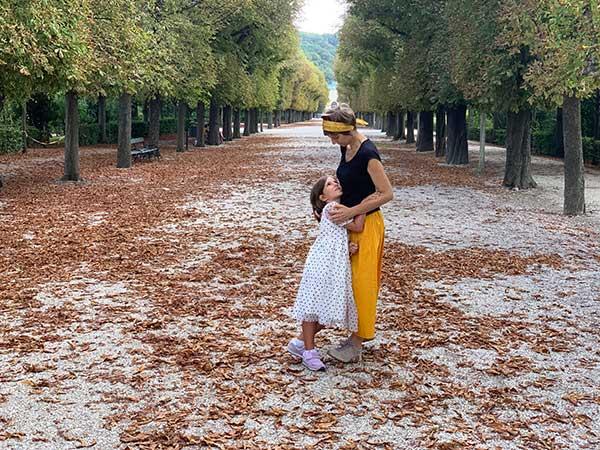 mamma e bambina tra foglie cadute nel parco di Schonbrunn