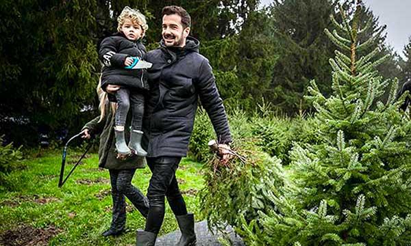 papà con bambi a sceglie albero di Natale