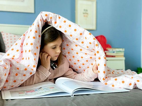 bambina legge libro sotto le coperte
