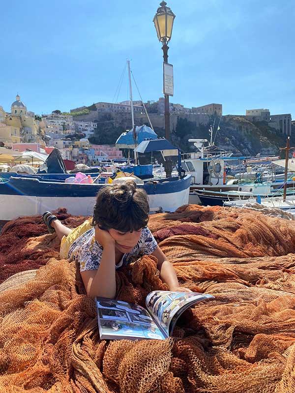 bambino legge libro su reti pescatori