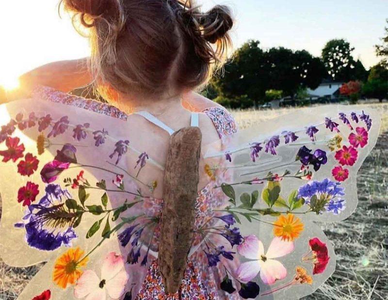 bambina con al idi farfalla